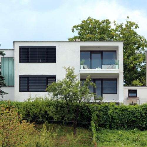 Newly built small modern family house with two glass balconies positioned on top of small hill surrounded with grass and trees