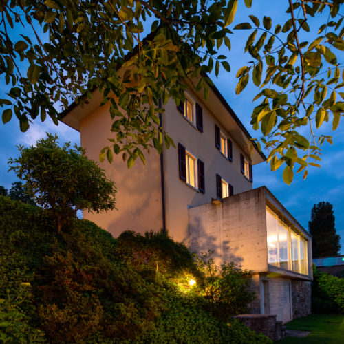 Beautiful house in the middle of the greenery with a modern reinforced concrete connection and a large window. The photo was taken in the evening and with a feeling of natural romance. The dream of a fairy tale.